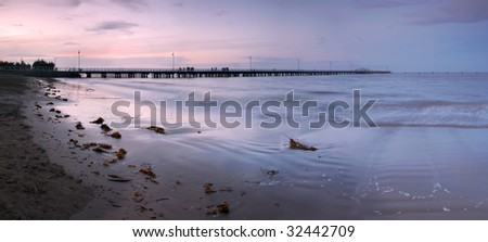 The sunset light is fading over the long pier - stock photo