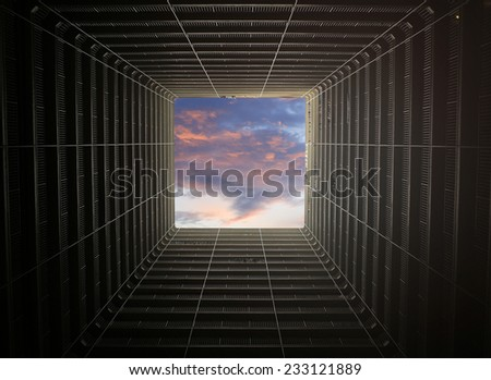The sunset sky inside the building, looking up from the ground - stock photo