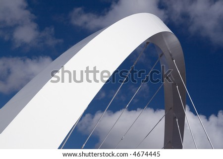 The supporting arch of the Clyde Arc bridge in Glasgow, Scotland, against blue sky and clouds - stock photo