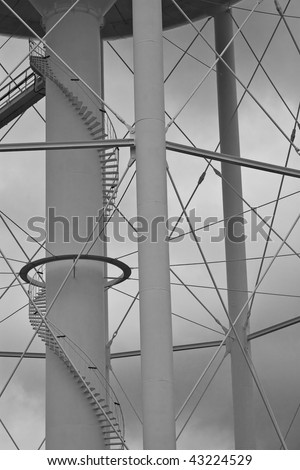 The supporting columns beneath a water tower, including the winding staircase that leads to the top.  A black and white treatment has been applied to the image, giving the overcast sky more mood.
