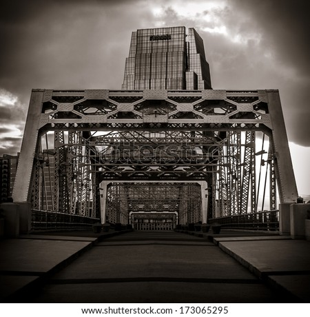 The supports of the walking bridge in downtown Nashville with a tall skyscraper in the background - stock photo