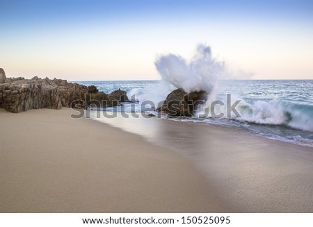 The surf crashes against a rocky seashore. - stock photo