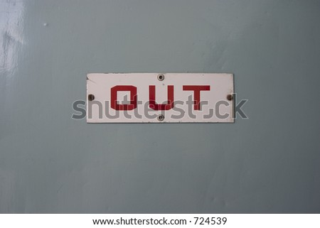 "The surface of a door with an ""out"" sign on it."