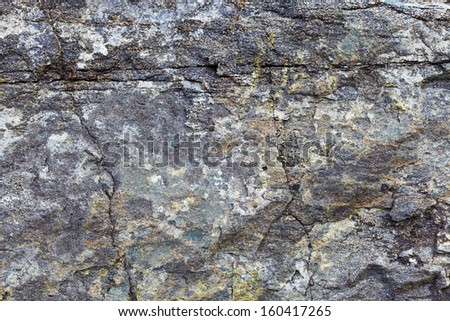 The surface of the granite rock with stains and cracks - a natural background - stock photo