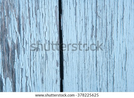 The surface of vertical blue planks with peeling paint on the wall of a wooden house