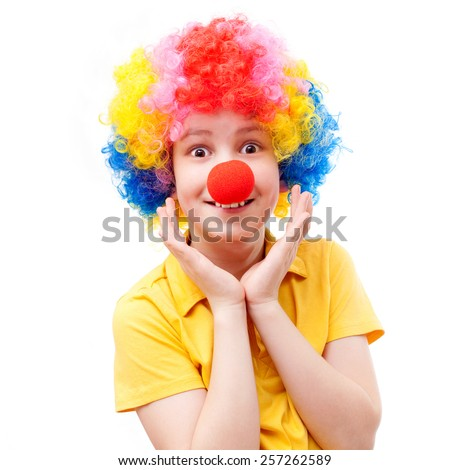 the surprised boy with a red clown nose and bright wig - stock photo