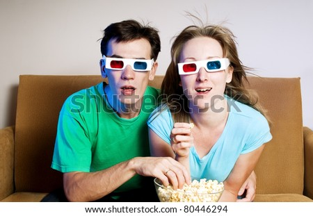 The surprised man and the woman watch TV - stock photo