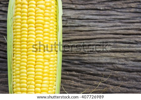the sweet corn with wooden background - stock photo