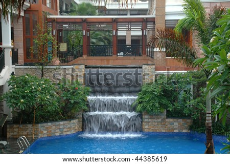 The swimming pool and waterfall in hotel (resort) - stock photo