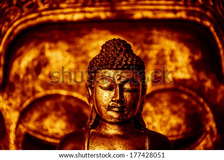 The symbol of the richness, of the founder of Buddhism, Buddha miniature statue sculpture with golden painted wood carved Buddha face on the background, with red effect - stock photo
