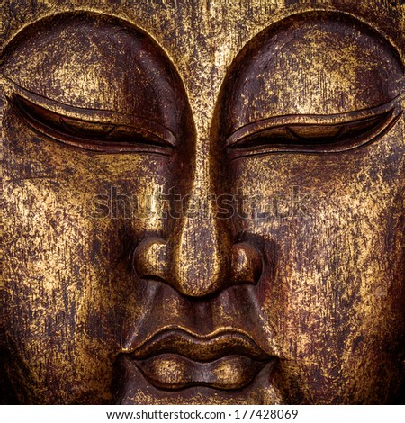 The symbol of the richness, of the founder of Buddhism, Buddha portrait golden painted wood carved statue sculpture close up - stock photo