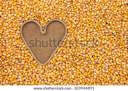 The symbolic heart made of rope lies on sackcloth and maize, with space for your text - stock photo