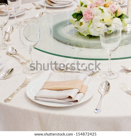 The table is set for a western style dinner with round glass on table - stock photo