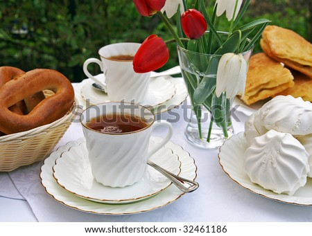 The table set for afternoon tea in a summer garden - white tea-things, pastry, marshmallows, flowers in a vase, blur background - stock photo