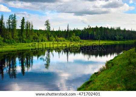 The taiga river with a quiet current and clouds reflected in it, Russia, Yakutia
