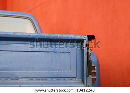 The tailgate of a blue battered sixties American Pickup Truck in front of a red wall - stock photo