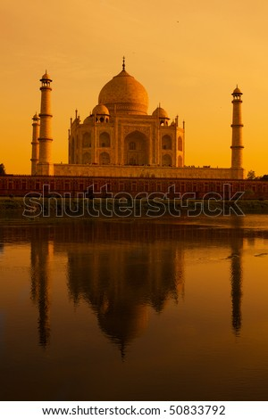 The Taj Mahal reflecting in the holy Yamuna river at sunset. - stock photo