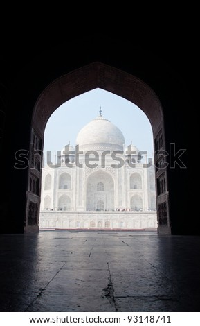The Taj Mahal seen through a door in the east gate - stock photo