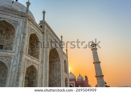 The Taj Mahal The Taj Mahal ,one of it's beautiful minaret and a mosque .The Taj Mahal is the epitome of Mughal art and one of the most famous buildings in the world, it is an UNESCO heritage site. - stock photo