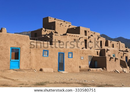 The Taos pueblo in New Mexico features adobe structures stacked atop each other. - stock photo