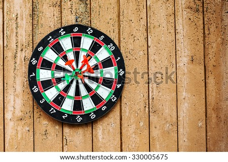 The target on a wooden wall with darts