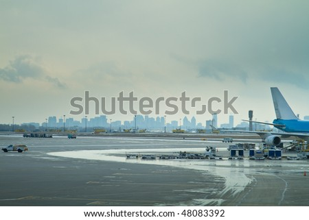 The tarmac at an airport, showing the rear of a passenger plane and service vehicles surrounding it, with a skyline of a city behind.  Pearson International airport, Toronto, Ontario.