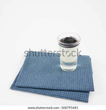 The tasty homemade blueberry panna cotta (Italian pudding dessert) in the small glass on blue cotton fabric. - stock photo