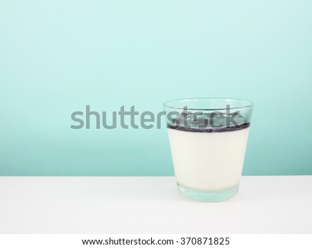 The tasty homemade blueberry panna cotta (Italian pudding dessert) in the small glass on white table. - stock photo