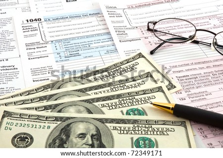 The tax forms with the glasses, money and the pen. - stock photo