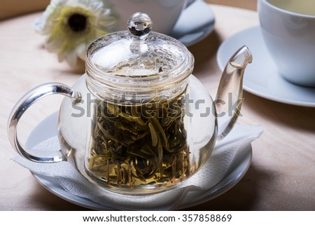 The tea time. Jasmine tea or herbal tea  in a transparent teapot, cups, wooden background, close up. - stock photo