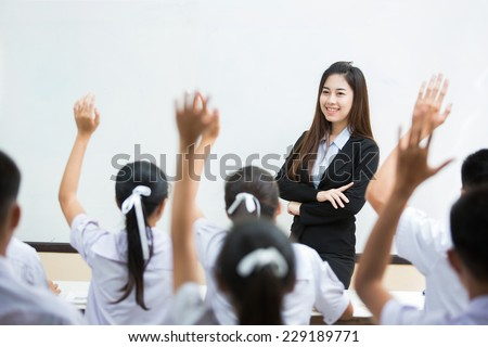 The teacher asks students All students can answer questions. It raised questions - stock photo