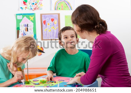 The teacher helps children to art lessons