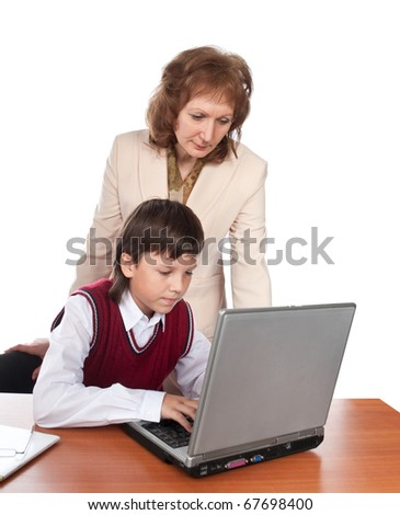 The teacher watches of the pupil working on the computer - stock photo