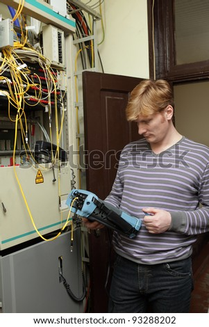 The technician measuring fiber optic at a server room - stock photo