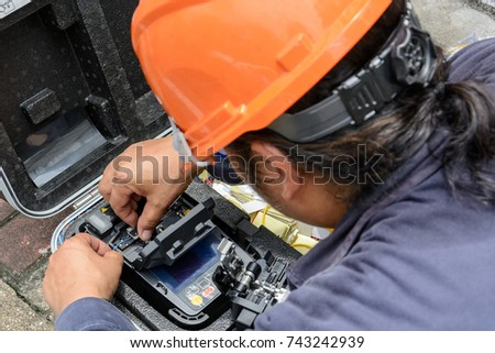 The technicians welding optical fiber cable with fusion splicing fiber optic Machine.