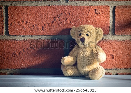 the teddy bear sit in front of a brick wall - stock photo