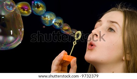 The teenage girl is blowing soap-bubbles on the black background