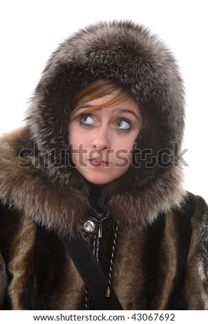 The teenager costs in a fur coat and a cap, looks aside - stock photo
