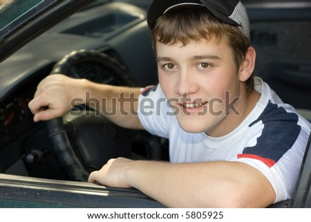 The teenager - driver affably looking from interior of the automobile