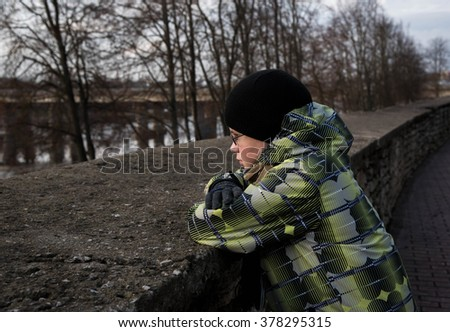the teenager is situated on the bank of the river. look aside. selective focus