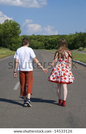 The teenagers are walking a wide road