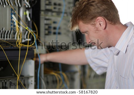 The telecom engineer looks on the multiplexer - stock photo