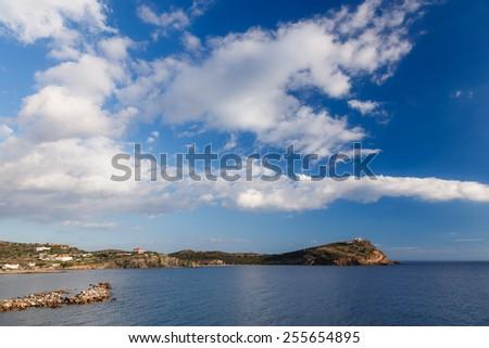 The Temple of Poseidon at Sounio, Greece against a blue cloudy sky, shot taken from accross the bay, long exposure photo - stock photo