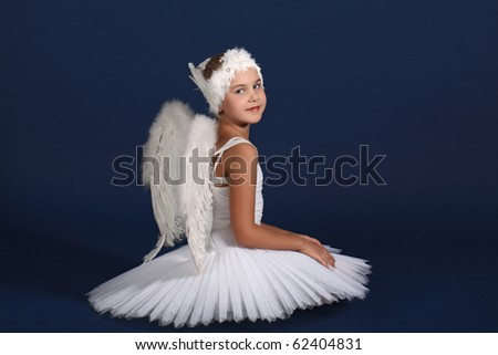 The ten years' girl sits in a ballet tutu on a dark blue background - stock photo