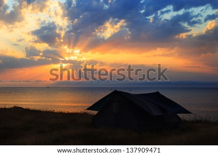 The tent on the seashore at sunset - stock photo