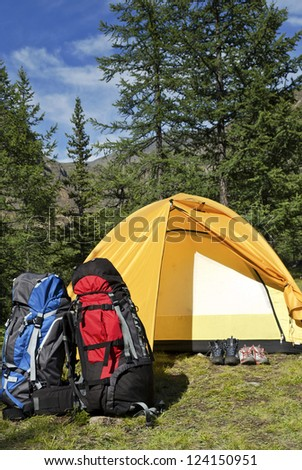 the tent, two backpacks and two pairs boots near a tourist track in mountains - stock photo