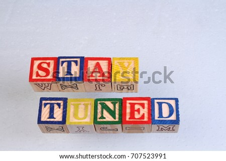 The term stay tuned displayed visually on a white background using colorful wooden toy blocks in landscape format with copy space