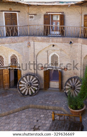 The terrace in old Caravan Saray is decorated with the silk carpets, made in traditional style. Bukhara, Uzbekistan, Central Asia. Bukhara is one of the cities on an ancient silk road. - stock photo