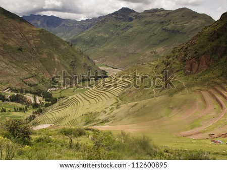 The terraced fields of the Sacred Valley of the Incas near Cusco, Peru, are active agricultural and archaeological sites.  An active dig, and the dust it creates, is visible in the lower right corner. - stock photo