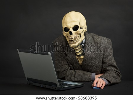 The terrible skeleton in a suit sits at black office with the laptop - stock photo